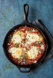 Shakshuka with Red Lentils and Feta Cheese - Overhead hero shot in cast iron skillet on blue blackground