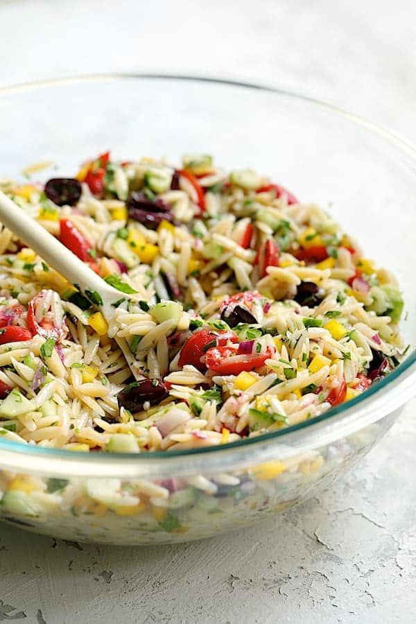 Greek Orzo Pasta Salad - Straight-on shot of salad being mixed together with white spoon in glass bowl