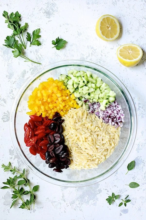 Overhead shot of all the ingredients for Greek Orzo Pasta Salad in glass bowl not yet mixed together