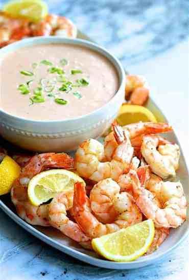 Shrimp Cocktail Louis - Close-up shot of shrimp on white platter with sauce garnished with lemon wedges