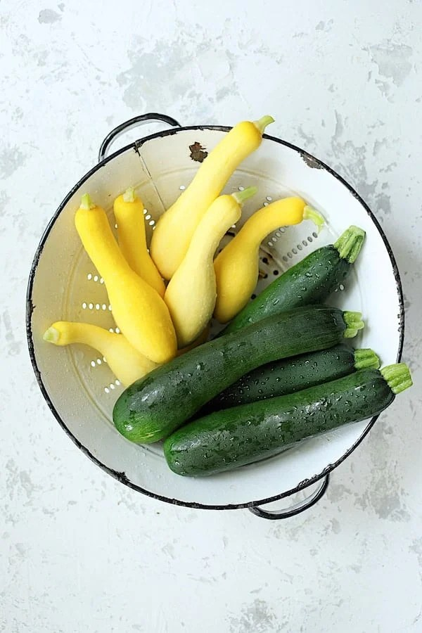 Overhead shot of zucchini and yellow squash in white colander on white background