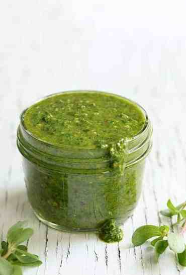 Purslane Chimichurri - Close-up shot of finished sauce in glass jar on white background with some spilling out