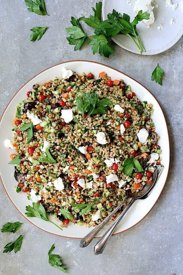 Mediterranean Farro Salad - Overhead hero shot of salad on round platter garnished with parsley