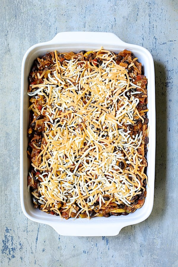 Black Bean and Yellow Squash Enchilada Casserole - Overhead shot of casserole in white baking dish with cheese added