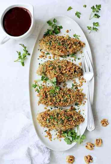 Walnut-Crusted Chicken with Pomegranate Sauce - Overhead hero shot of dish on white oval platter garnished with parsley and walnuts with sauce on white background