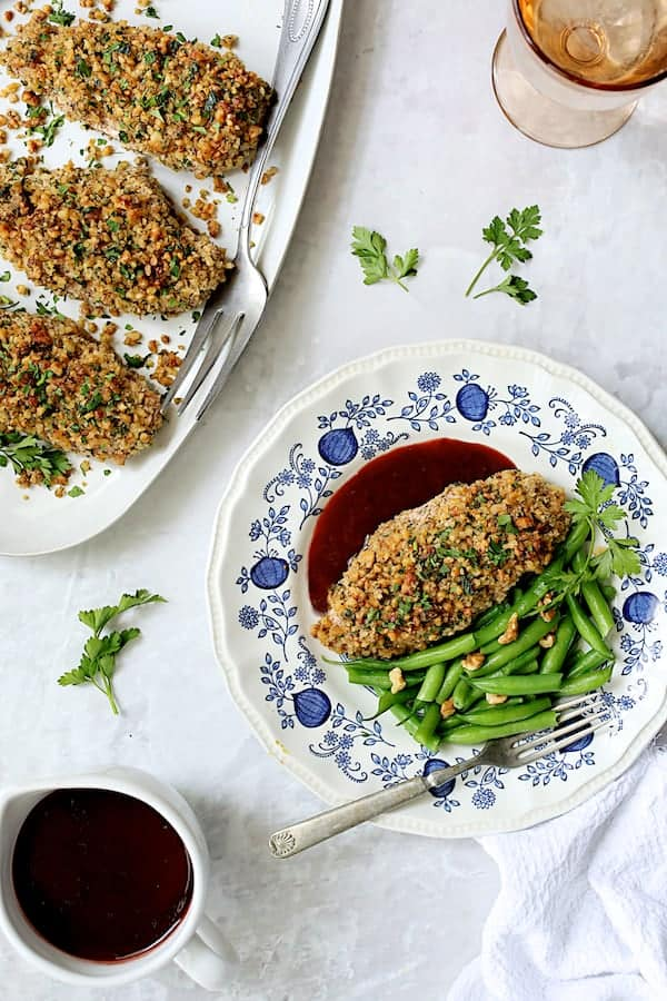 Walnut-Crusted Chicken with Pomegranate Sauce - Overhead shot with one breast served up on blue and white plate with sauce and green beans