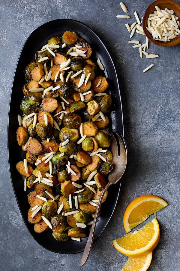 Pan-Roasted Brussels Sprouts with Thai Sweet Chili Orange Glaze - Overhead shot with slivered almonds and orange wedges