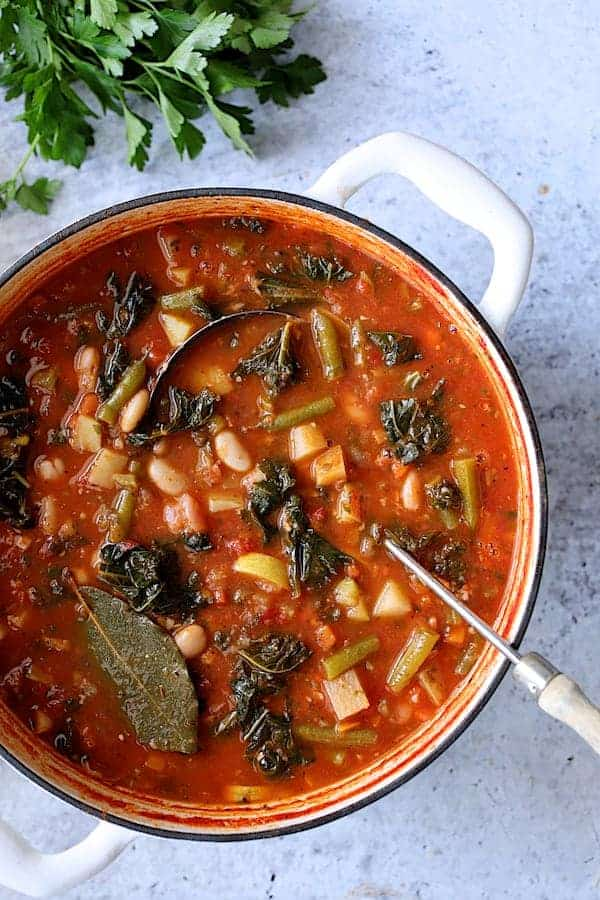 Italian Vegetable Stew - Overhead shot of soup in white Dutch oven on pale blue background with soup ladle