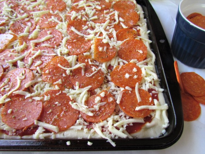 Unbaked pizza with cheese and pepperoni