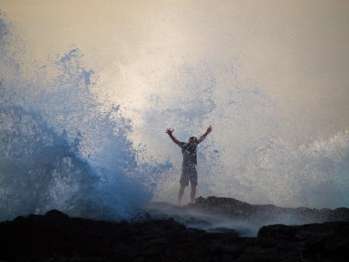A man stands in the middle of a wave spray as it crashes against the rocks