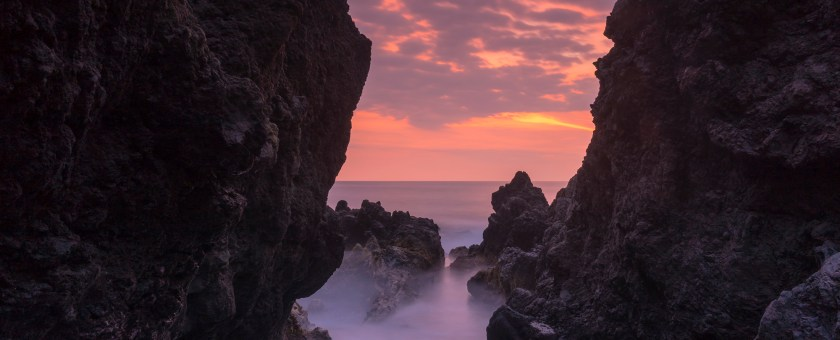 A bright colorful sunset through the dark rocks of Keauhou