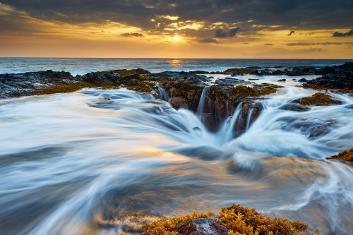 Waves rush around a large hole in the reef during a golden Hawaiian sunset