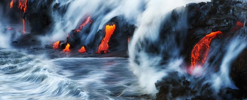 Kilauea 61G lava flowing into the ocean as smoke and steam rises over the rocks.