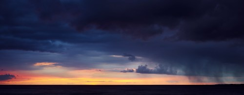 Dark clouds during a colorful sunset over the ocean