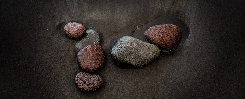 Rocks are nestled in the black sand of the Pololu Valley beach