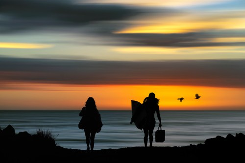 Surfer girls silhouetted against a beautiful Hawaii sunset