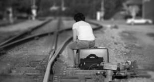 Mujer esperando en la vía del tren