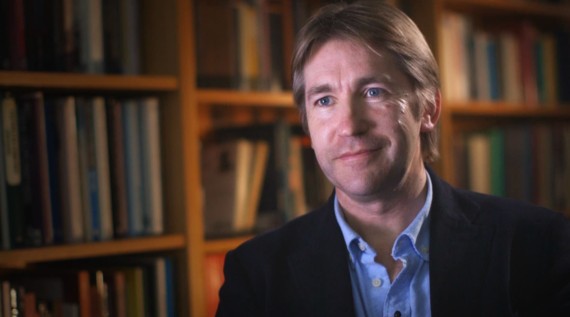 Historian Jonathan Phillips in front of a set of bookshelves