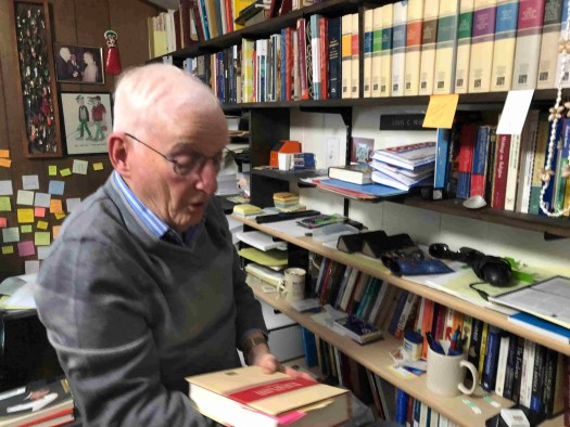 Louis Midgley holds a book in his Utah study.