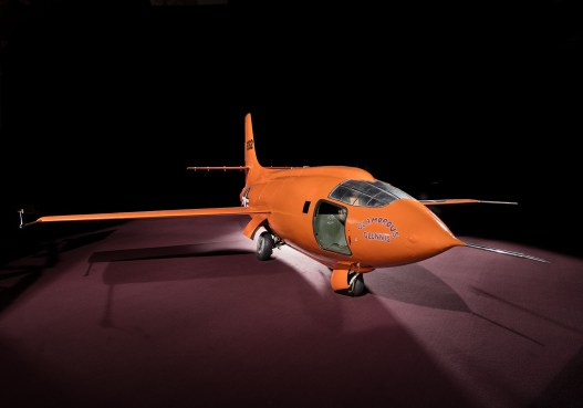 """Three-quarter right front view of the Bell X-1 """"Glamorous Glennis"""" (A19510007000) on the floor; artificially darkened background; Smithsonian National Air and Space Museum, Washington, D.C., November 16, 2015. Photo by Eric Long. [_T8A9671.2] [NASM2015-07331]"""