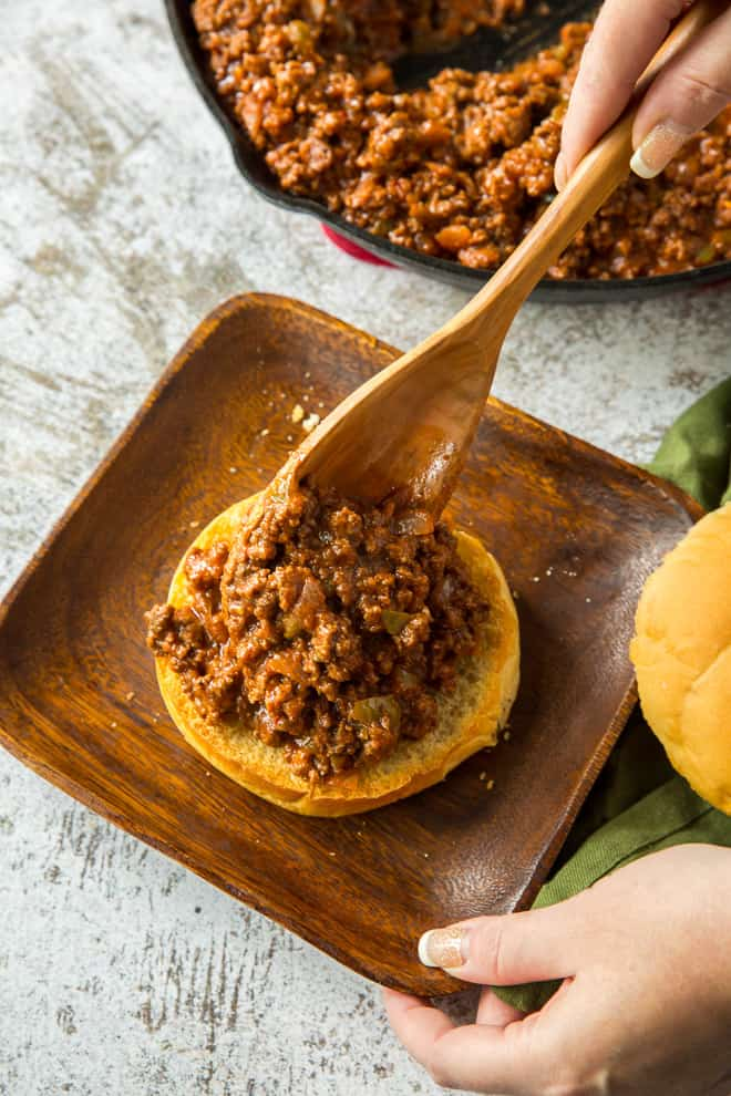 Spooning some of the sloppy joe mixture on to a bun