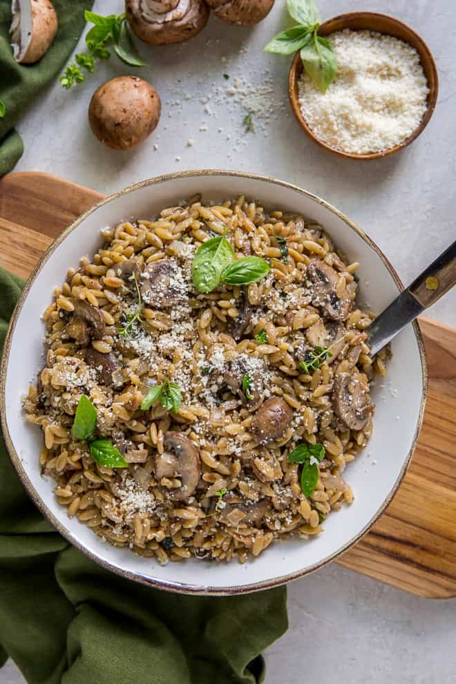 Creamy Orzo with Mushrooms and Parmesan in a serving bowl with a spoon.