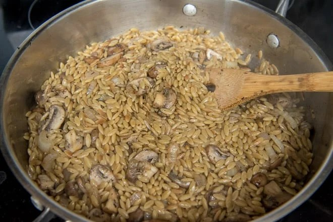 Chicken broth has been added to the orzo and then the mushrooms and onions go back in the pan.