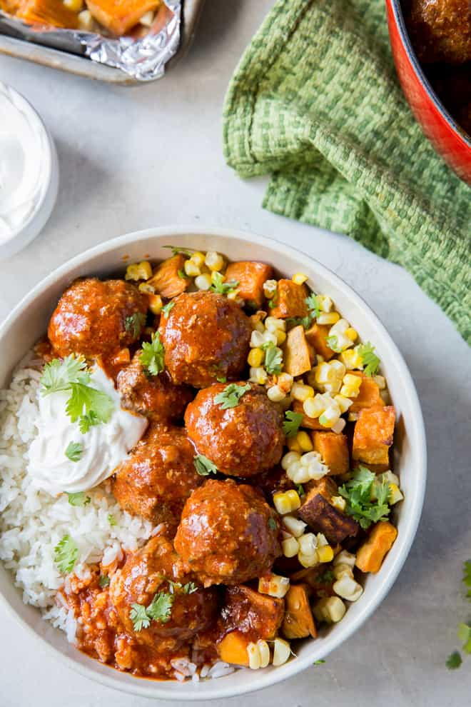 Tex-Mex Meatballs with Red Chile Sauce in a white bowl over rice with sweet potatoes and corn.