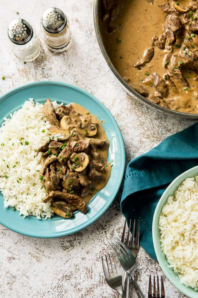A blue serving plate with a serving of rice and Beef Stroganoff.