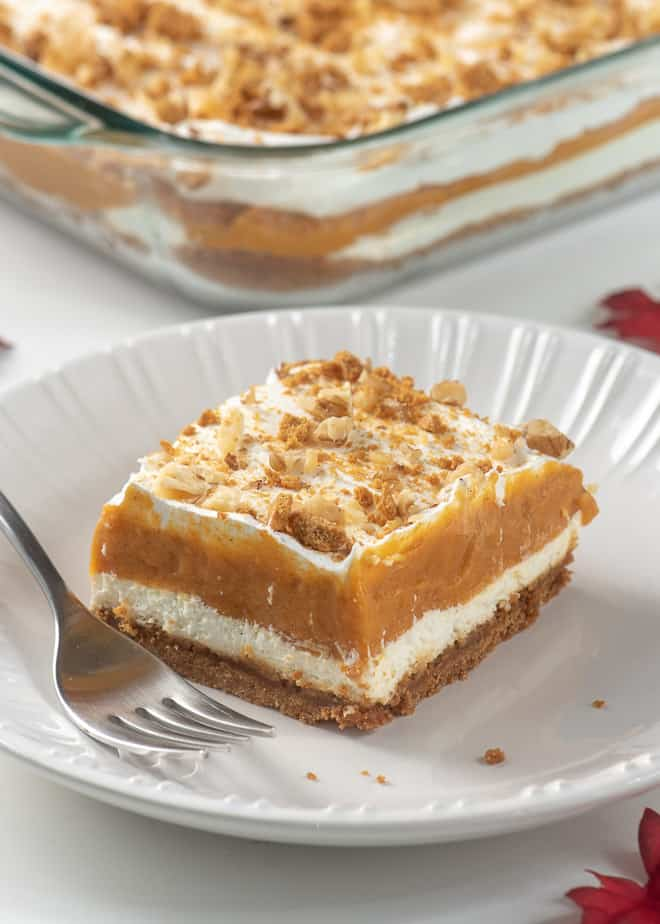 A slice of Creamy Layered Pumpkin Dessert on a white plate with a fork.