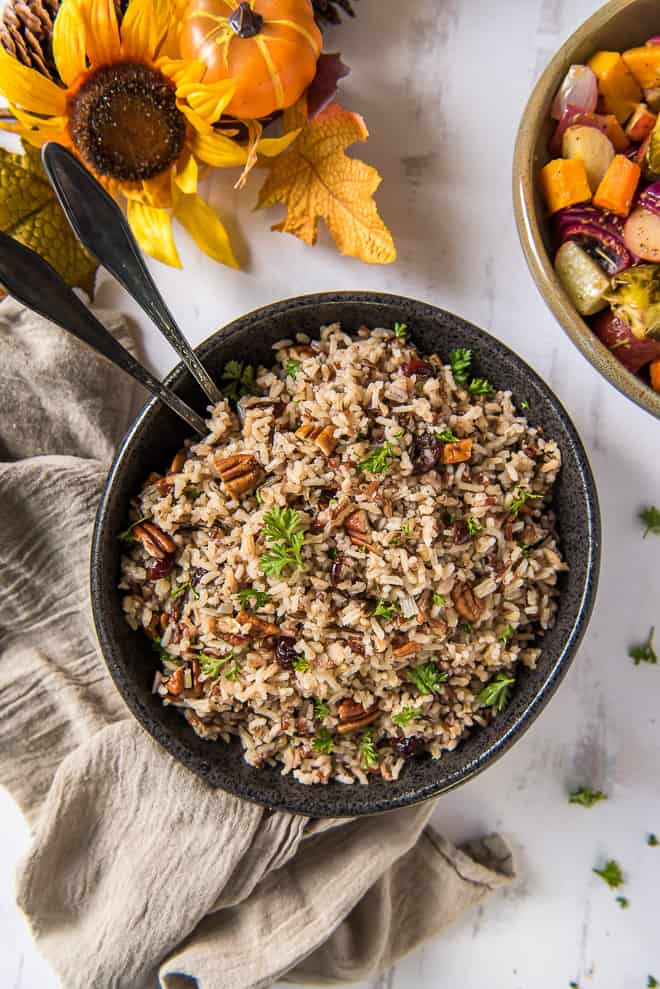 A black serving bowl filled with Wild Rice Pilaf with Cranberries and Pecans with sunflowers in the background
