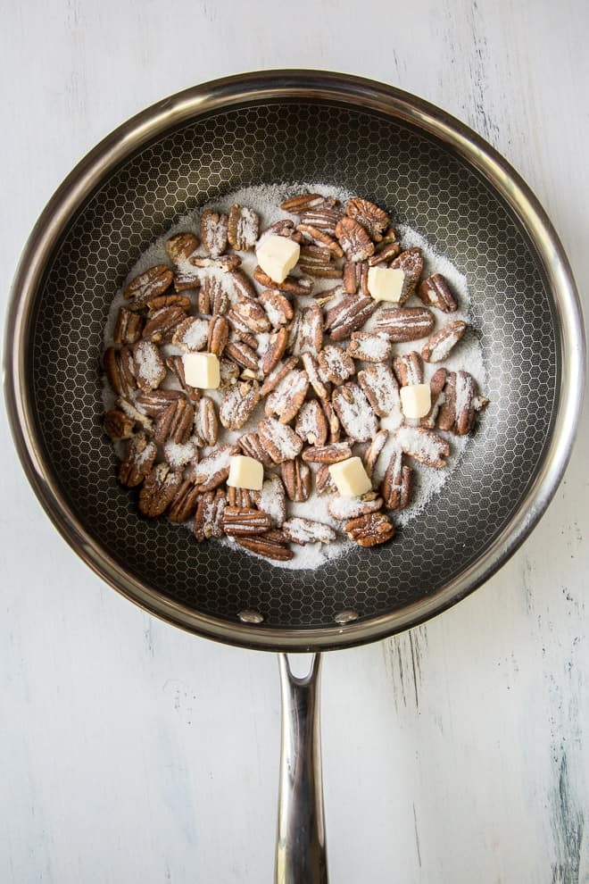 An in process image of nuts in a non-stick skillet with sugar and small pieces of butter.