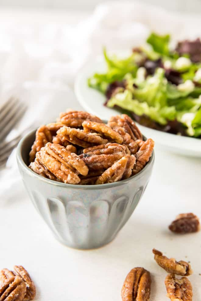 A small bowl full of Glazed Nuts with a salad in the background.