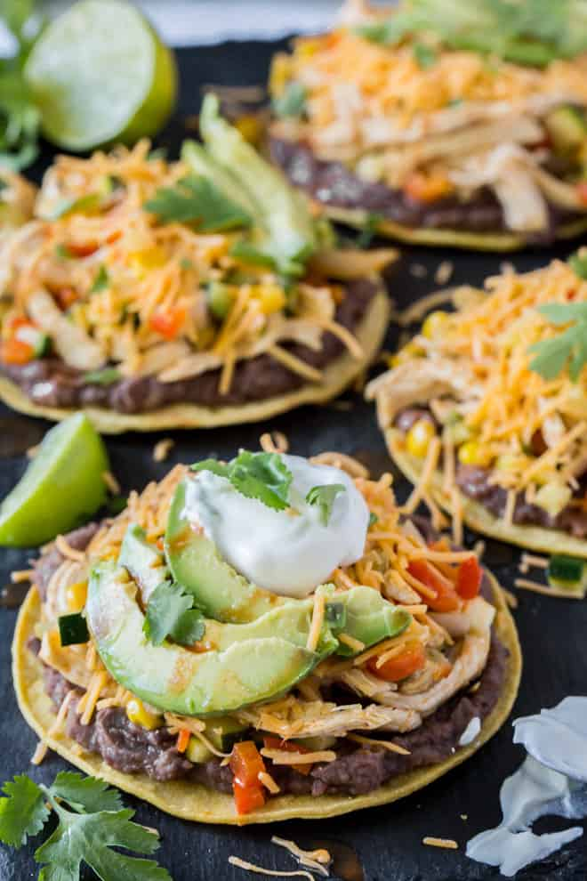 A close up image of a Chicken and Veggie Baked Tostada topped with cheese, avocado, and sour cream.