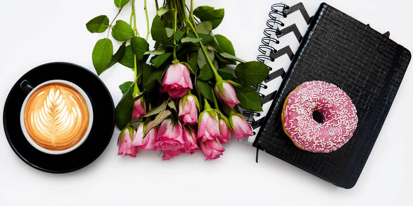Flat lay photograph with a latte in a cup and saucer, a bunch of pink roses, 2 black and white printed journals, and a pink frosted donut with white sprinkles