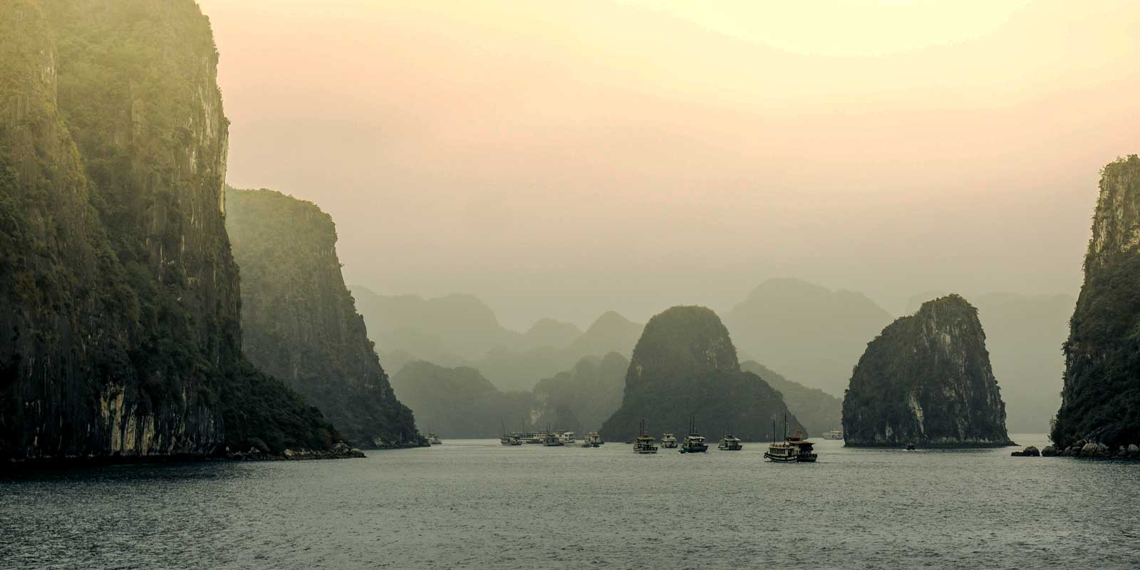 Marvel at the tall rock islands in Ha Long Bay in Vietnam.