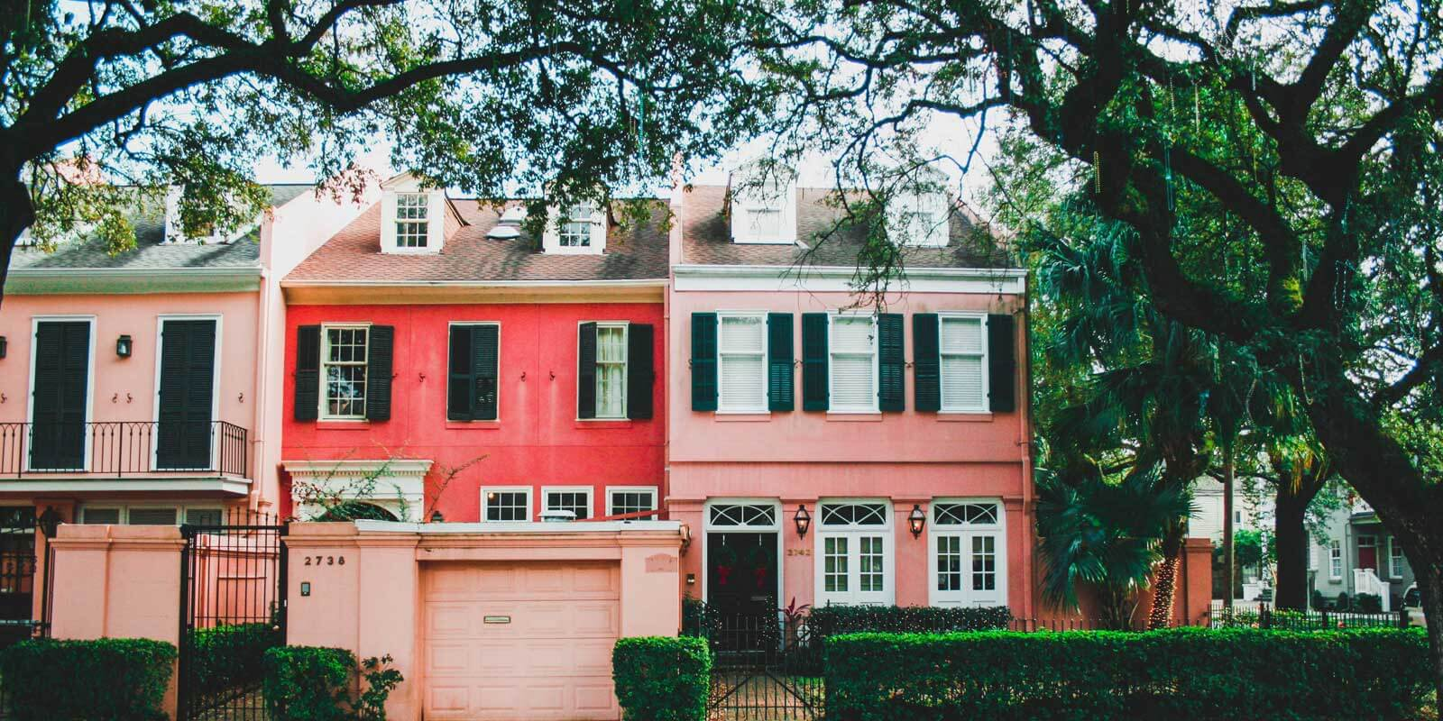 Salmon pink and florescent red townhomes set amidst trees and shrubs covered in Mardi Gras beads.