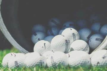 Close up photo of Nike golf balls spilling out of a bucket