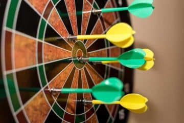 Closeup of a dart board with yellow and green darts