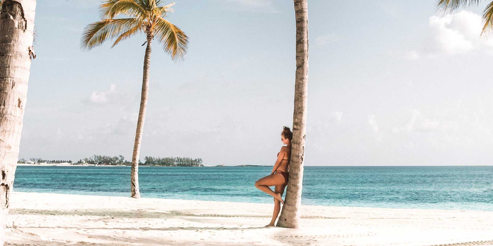 Woman leaning against a palm tree on a deserted beach in Sri Lanka