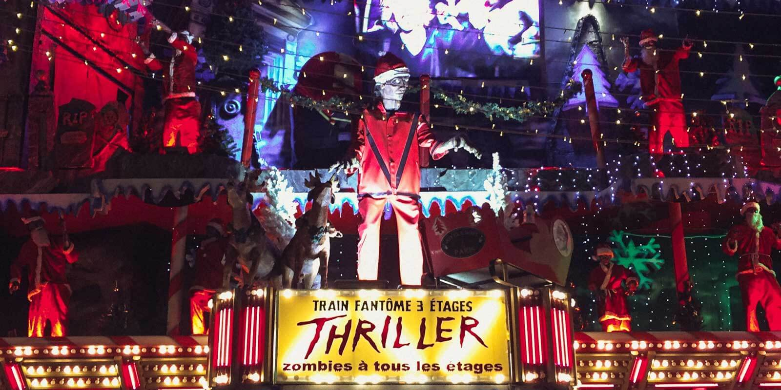 Closeup of the outside of a Christmas, zombie, and Michael Jackson's Thriller themed ride at a Christmas market in Paris.