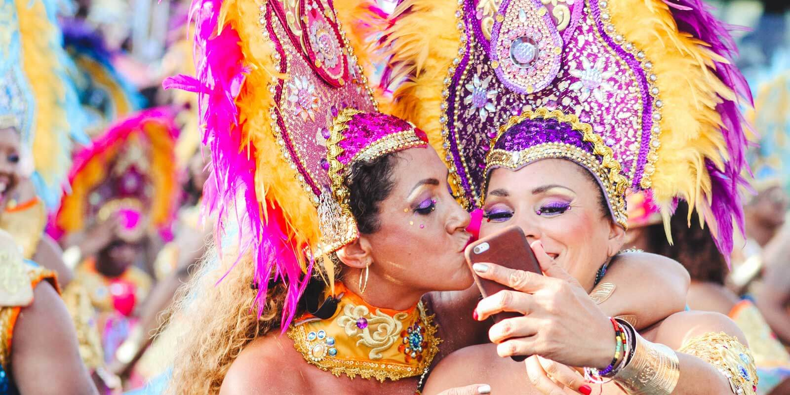 Two women in elaborate Carnival costumes and head dress taking a selfie with a phone.