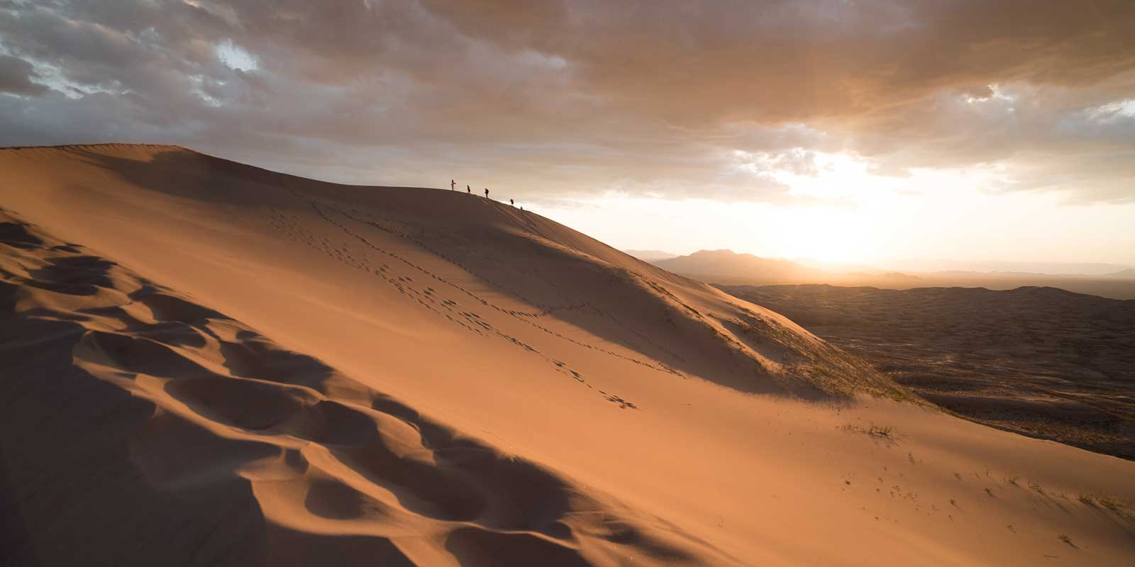 Landscape of the Mojave Desert with tiny silhouettes of people climbing the sand