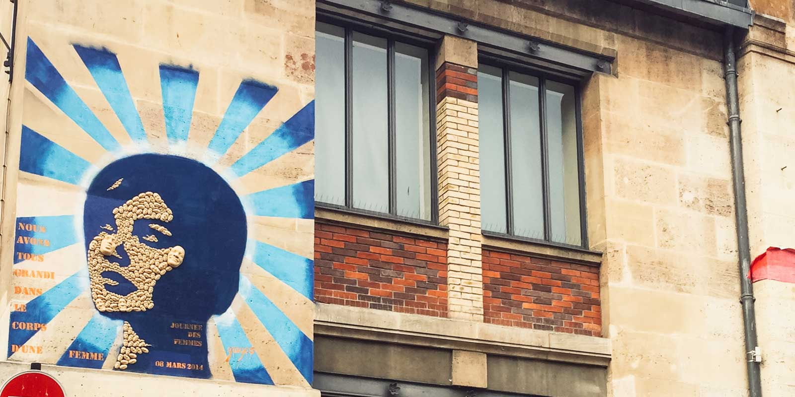 Street art on a building showing a silhouette of a woman's face made from smaller faces, with blue rays in the background.