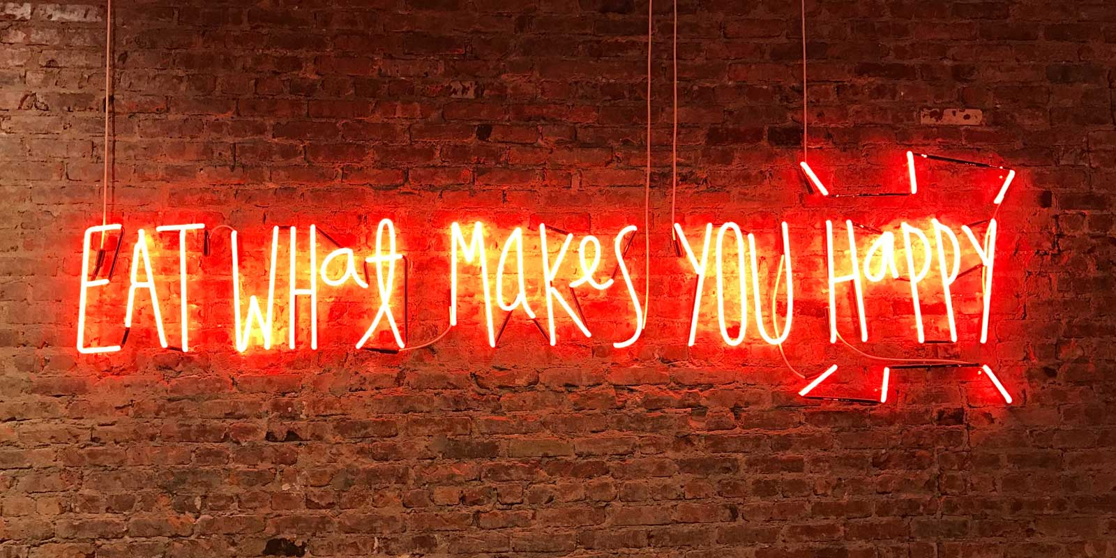 "Closeup of a neon sign that reads ""Eat what makes you happy."""