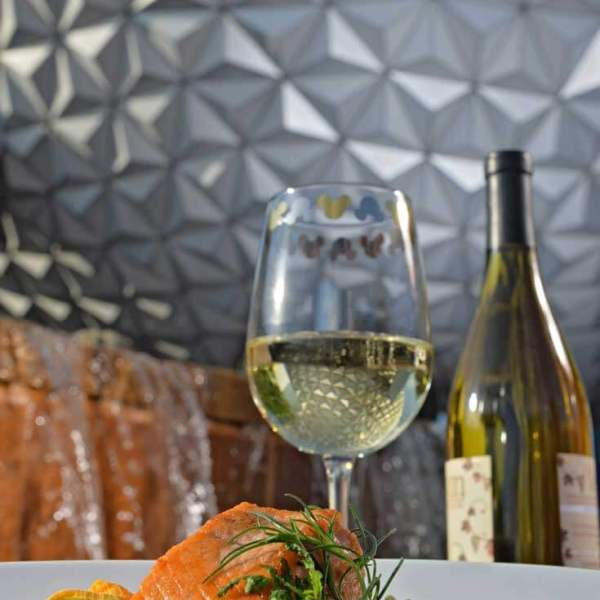 Closeup of a fancy international seafood dish with a glass of white wine with the iconic Epcot Globe in the background.