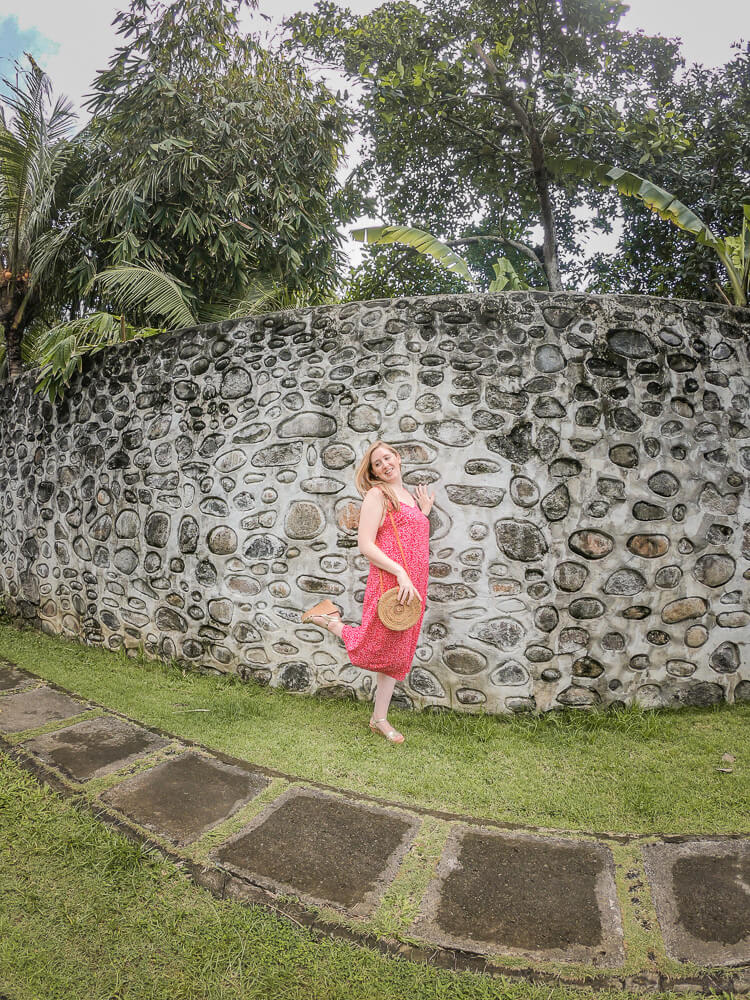 Travel blogger Meg Frost posing in front of a stone wall surrounded by tropical trees in Bali.