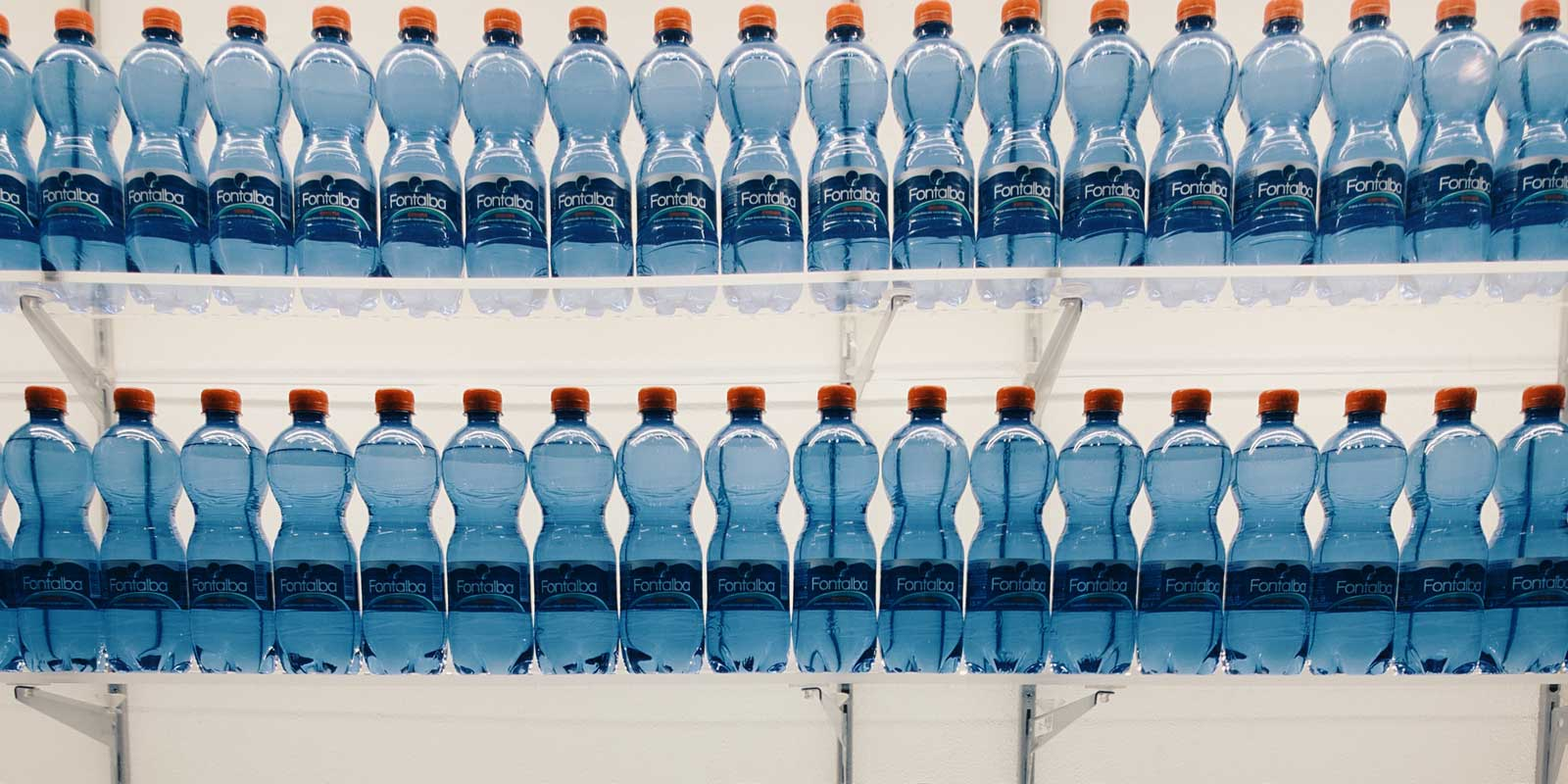 Photo of two shelves full of single use bottles of water.
