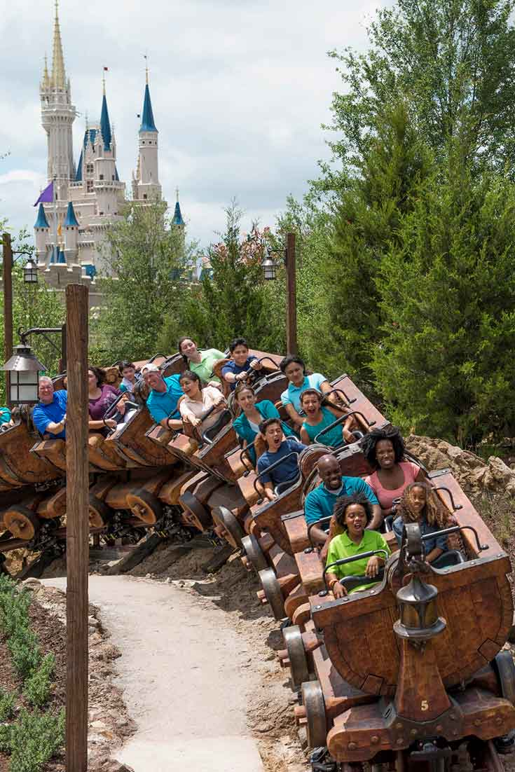 A group of people zip around a corner on the Seven Dwarfs Mine Train at Disney World's Magic Kingdom.