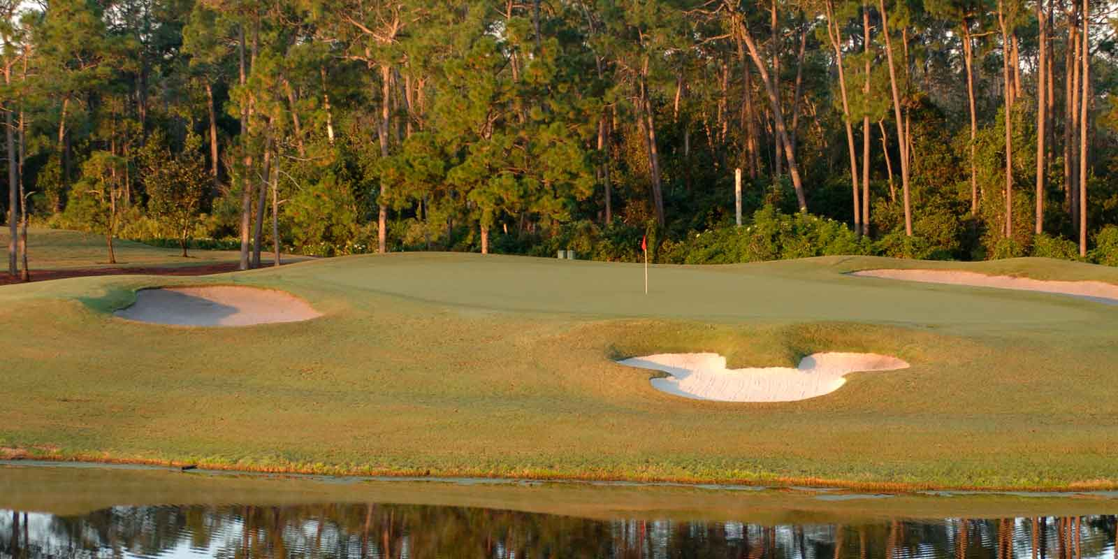 Landscape view of hole #6 at Magnolia Golf Course at Disney World, which features a Mickey Mouse shaped sand trap.